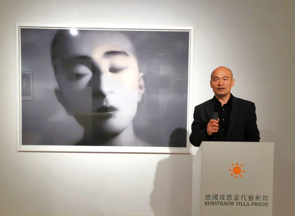 Der Leiter vom Kunstraum Villa Friede, Ren Rong, hält einen Einführungsvortrag